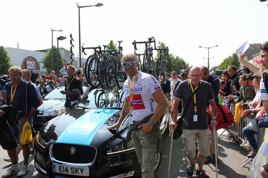 Geir foran en av Team SKY sine Jaguarer. Syklene på taket koster også noen kroner.