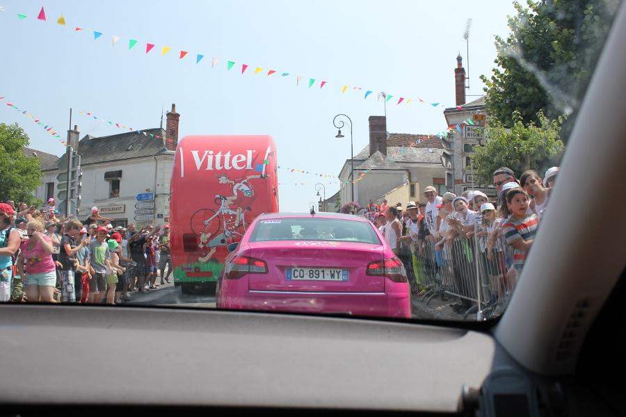 Folket pakker seg tett langs veien i timene før rytterne kommer. Reklamebiler og pressebiler kjører i lang rekke.